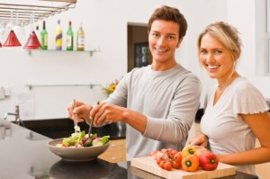 Smiling couple preparing salad together in kitchen